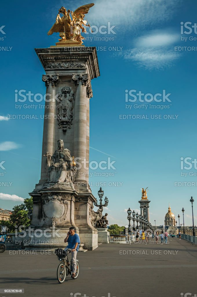 Cyclist on elegant Alexandre III bridge over the Seine River in Paris. stock photo