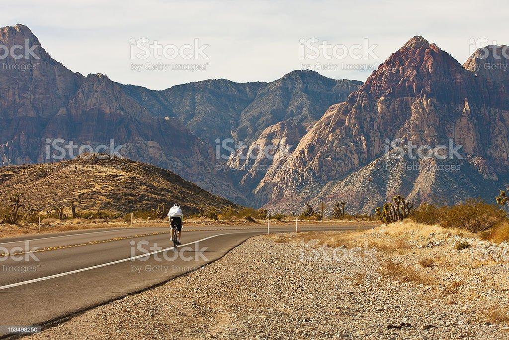Cyclist on Road Through Desert Into Mountains royalty-free stock photo