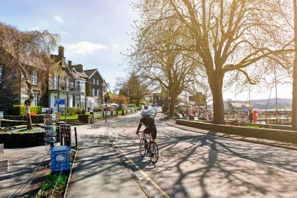 Cyclist on the lakeside street at Ambleside, a small lakeside town situated at the head of Windermere Lake within the Lake District National Park in England stock photo