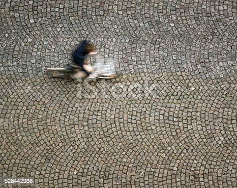 Motion blur on a cyclist as he rides over old-fashioned, patterned cobbles in Montparnasse, Paris.  Photographed from directly above.