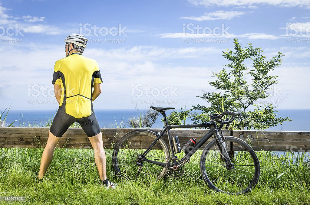 Cyclist peeing in the bushes during a Race stock photo