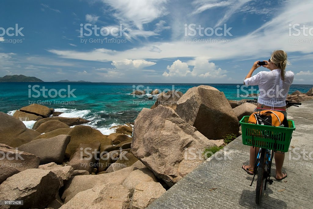Cyclist photographs ocean scene at La Digue royalty-free stock photo