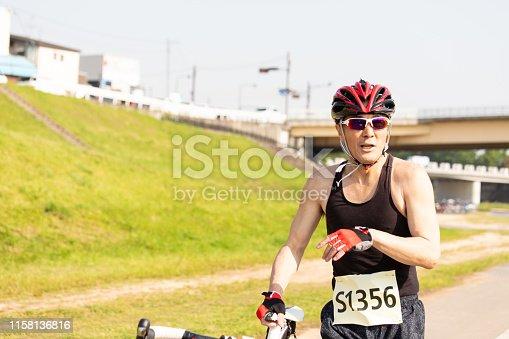 istock Cyclist pushing racing bike 1158136816