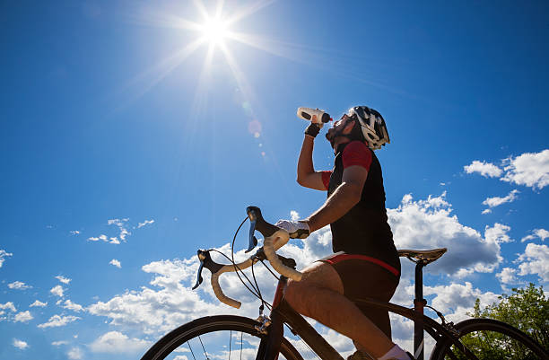 Cyclist resting and drinking isotonic drink. stock photo