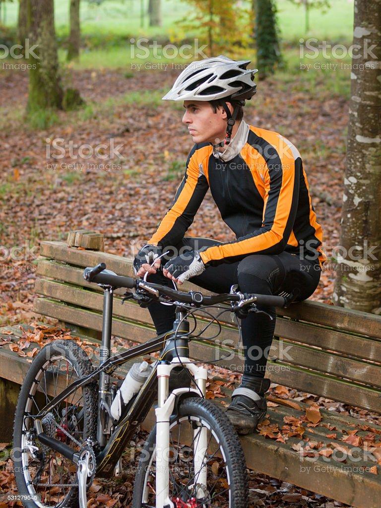Ciclista Descanse en un banco en la naturaleza. - foto de stock