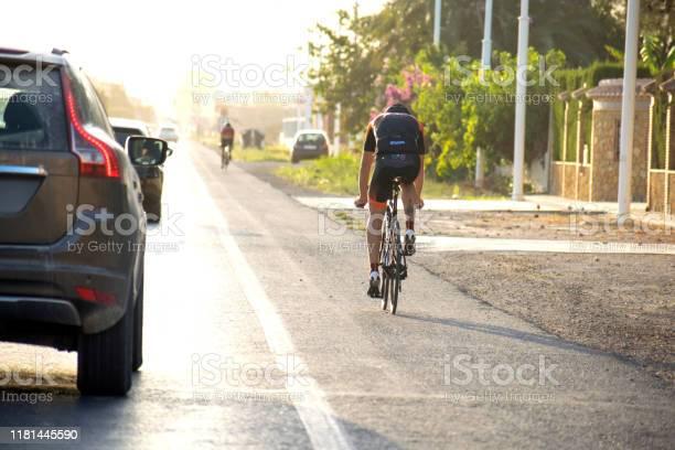 Ciclista Montar En Bicicleta En La Carretera A Lo Largo De Los Coches Que Pasan A Su Lado Y Mantener La Distancia De Seguridad Con Bicicletas Foto de stock y más banco de imágenes de 2019