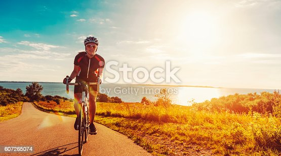 Close up of a female athlete who rides her bike up a steep hill. The sun shines as her feet hits the pedals and she drives the bicycle forward. In the background is the sun setting over the sea.