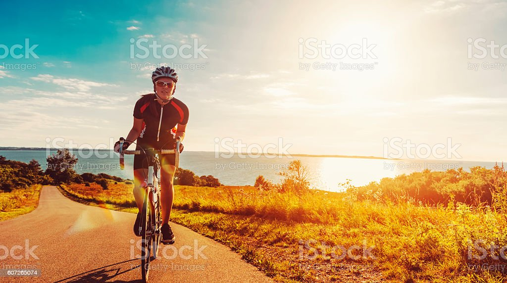 Cyclist rides her bike up a steep hill at sunset stock photo