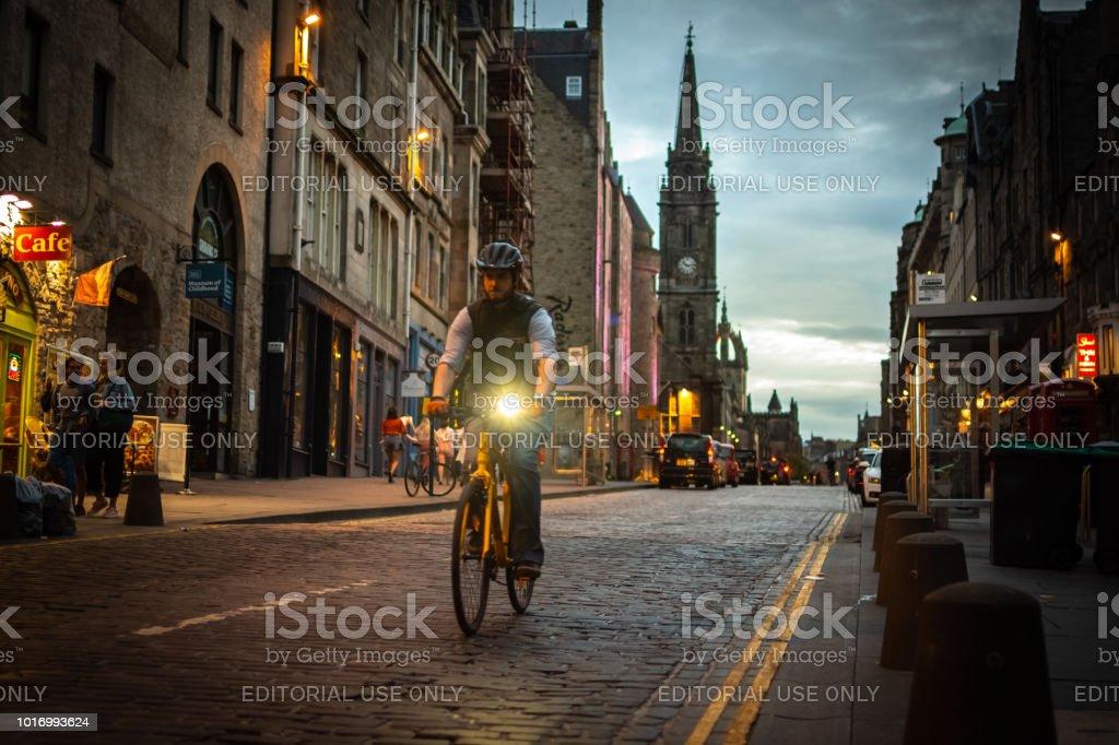 Cyclist rides his bike along The Royal Mile in Edinburgh, Scotland stock photo