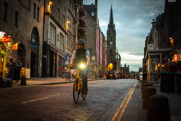 Cyclist rides his bike along The Royal Mile in Edinburgh, Scotland stock photo