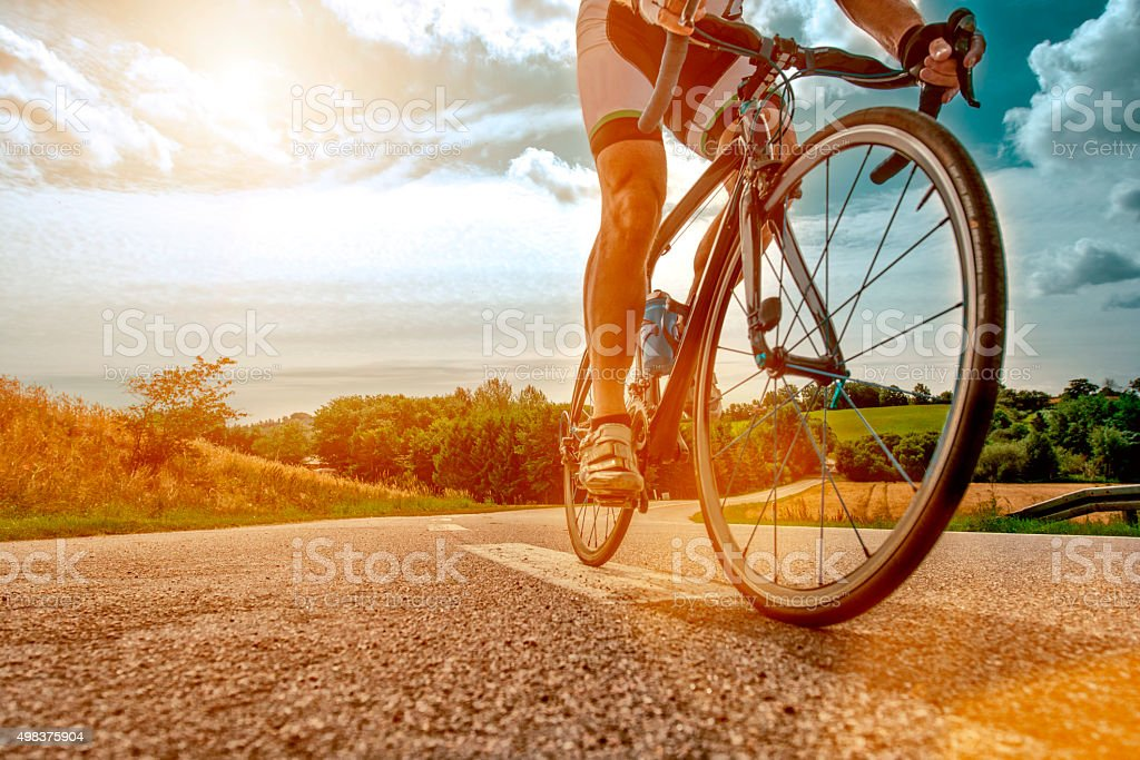 Cyclist rides his bike up a steep hill stock photo