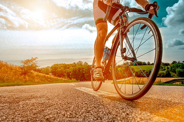 cyclist rides his bike up a steep hill - cycling stock pictures, royalty-free photos & images