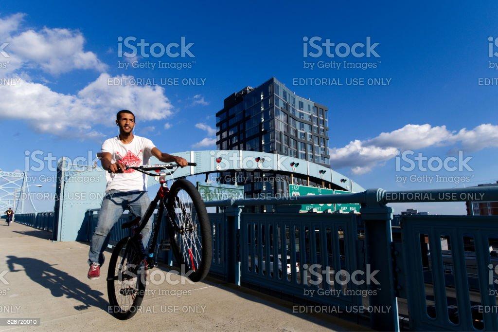 Cyclist rides on rear wheel on Ben Franklin Bridge stock photo