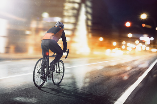 Cyclist rides through illuminated city