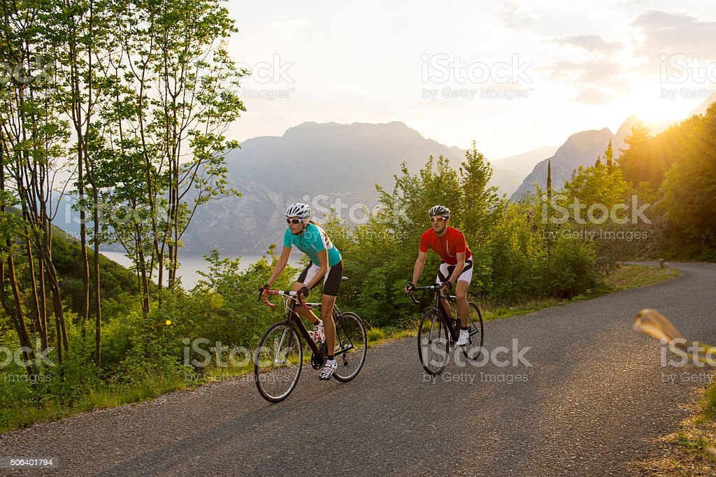 Cyclist riding a bike in behind the sunset stock photo