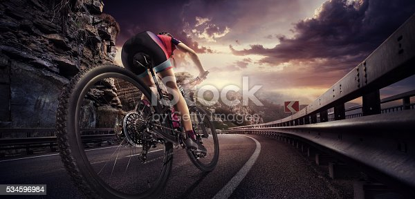 istock Cyclist riding a bike to the sunset on the highway 534596984