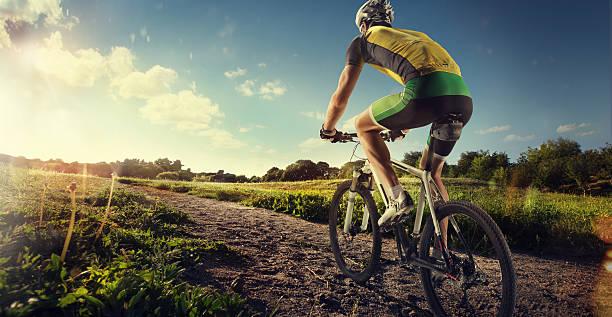 Ciclista andando de moto ao pôr-do-sol na ofroad - foto de acervo