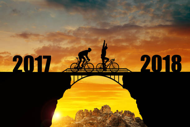 Cyclist riding across the bridge into the New Year 2018. Cyclist riding across the bridge at sunset. Forward to the New Year 2018. 2017 stock pictures, royalty-free photos & images