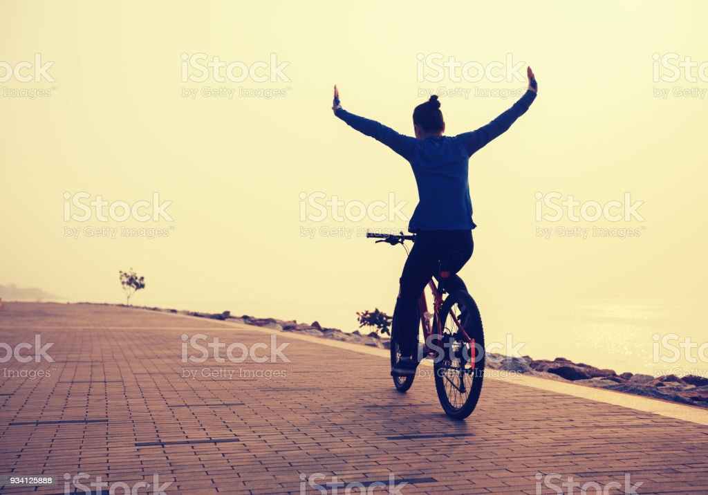 cyclist riding bike with arms outstretched in the coasts sunrise – zdjęcie