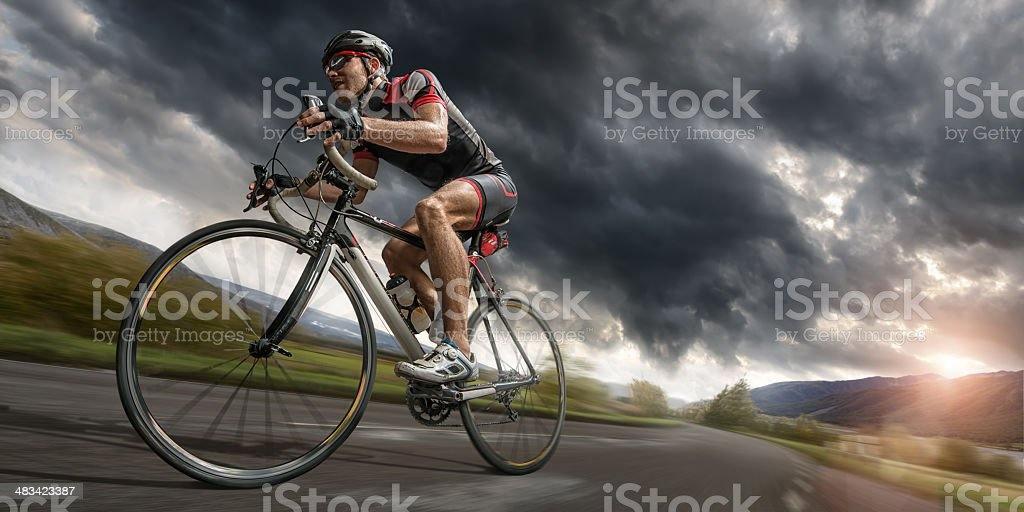 Cyclist Riding Hard To Outrun Storm stock photo