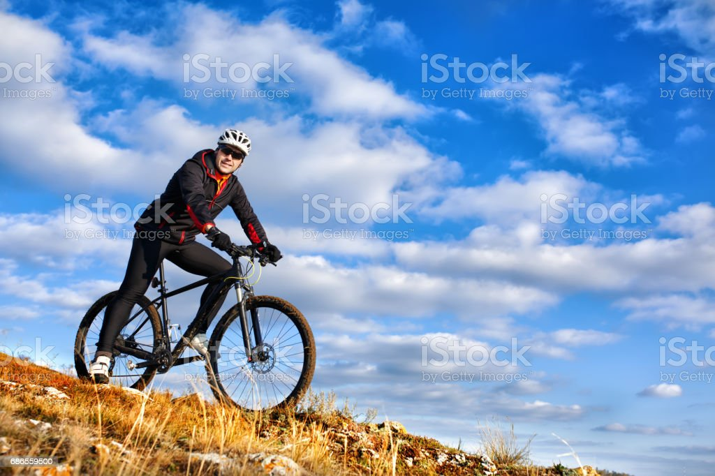 Cyclist riding his bike down on mountain trail. Beautiful sky and clouds on background royalty-free stock photo