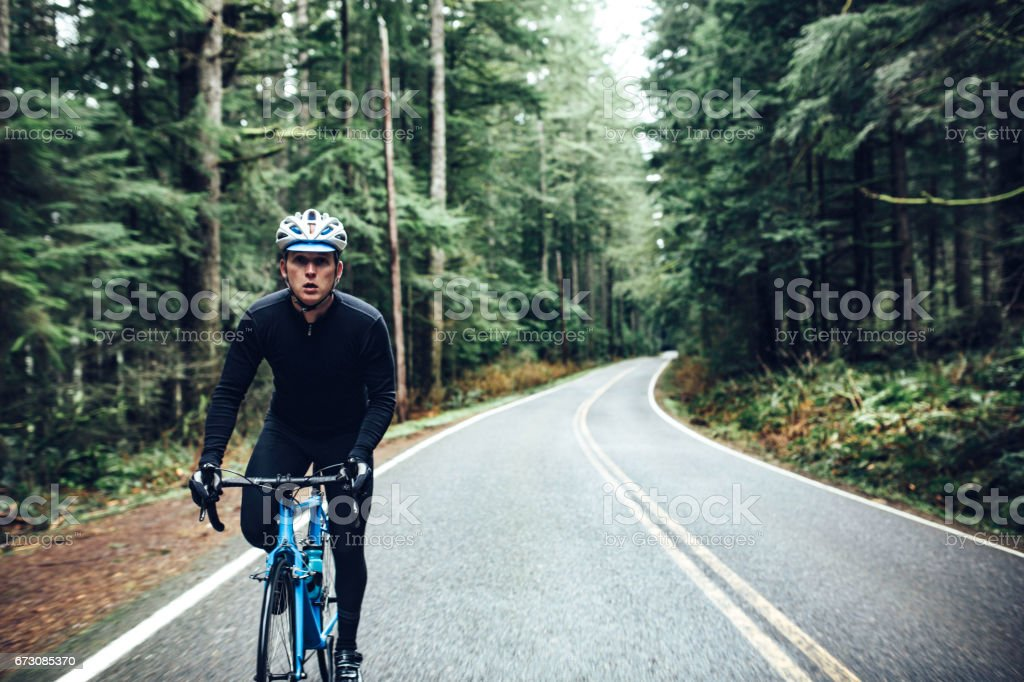 A man cycling in a beautiful Oregon state forest setting on the road...