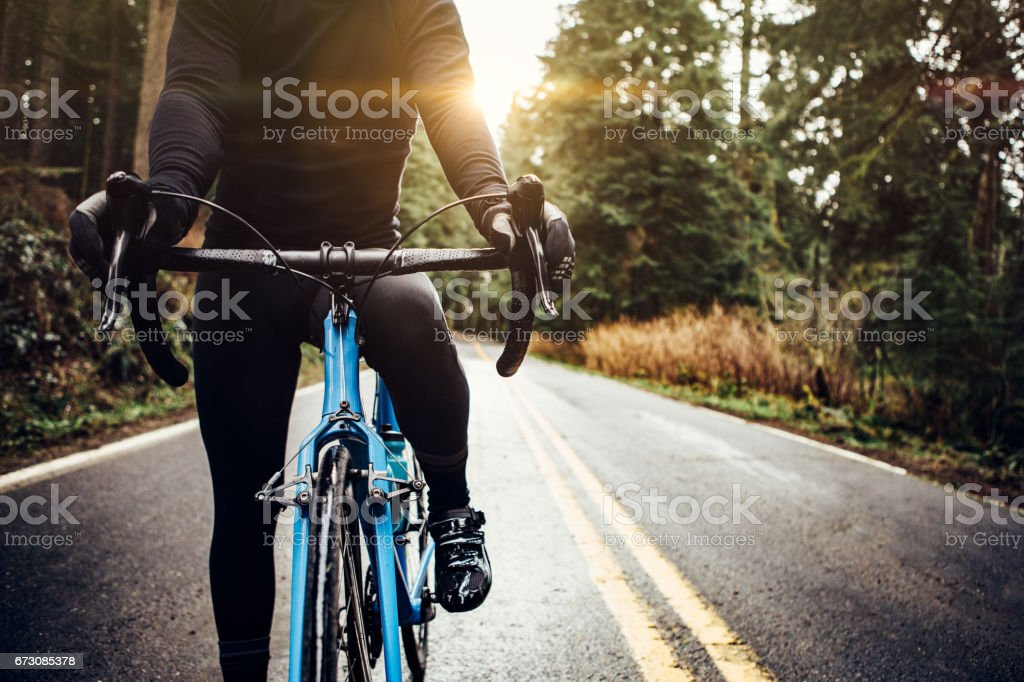 Cyclist Riding Mountain Road on Racing Bike - foto stock