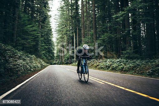 A man cycling in a beautiful Oregon state forest setting on the road to Larch Mountain. He has a bright blue street bike that stands out from the green of the surrounding trees. He looks up the road ahead as he pedals hard downhill, getting in some training for upcoming races.  Motion blur on the road as he speeds down.