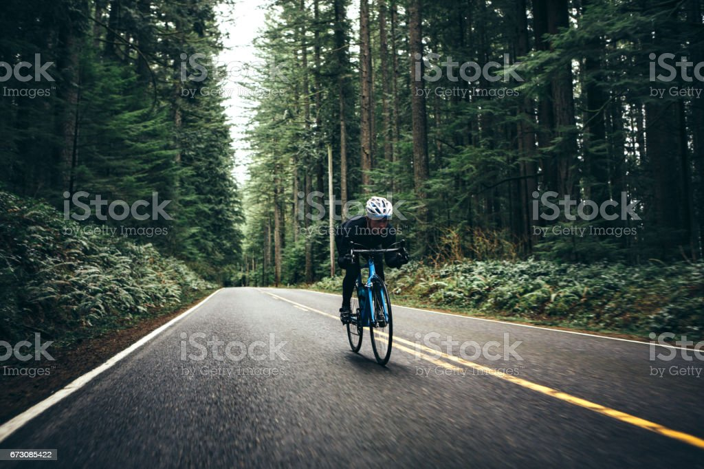 Cyclist Riding Mountain Road on Racing Bike - foto stock