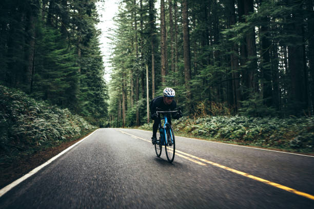 Cyclist Riding Mountain Road on Racing Bike stock photo