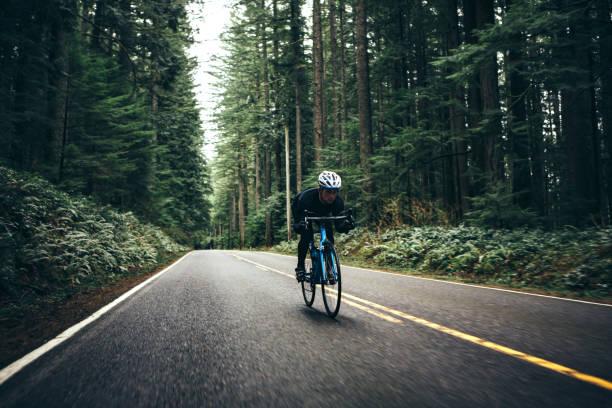 radfahrer fahren bergstraße auf rennrad - straßentraining stock-fotos und bilder
