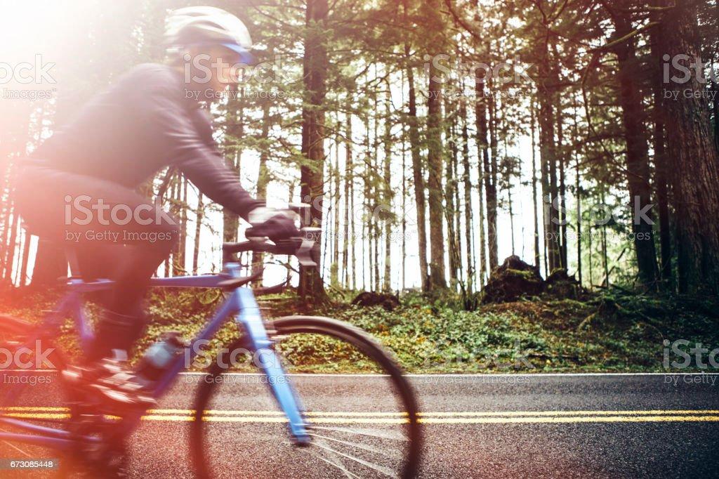 Cyclist Riding Mountain Road on Racing Bike stock photo