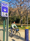 Valencia, Spain - November 25, 2020: Woman riding bike next to SOS post in the Turia Garden. This system is controlled by the police and used in case of need by the park visitors
