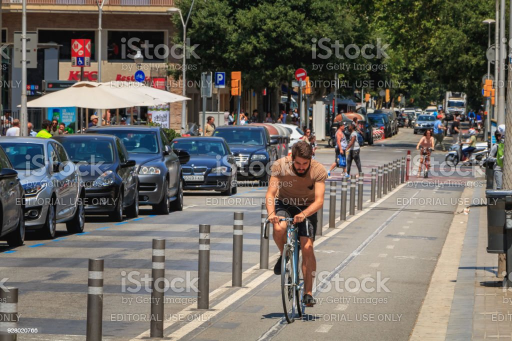 cyclist riding on a bike lane on a summer day stock photo