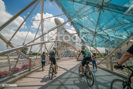 Singapore City, SINGAPORE - FEB 10, 2017: Cyclists riding bicycles on helix bridge with Marina Bay Sands in background. Tourism in Singapore is major industry and contributor to Singapore economy.
