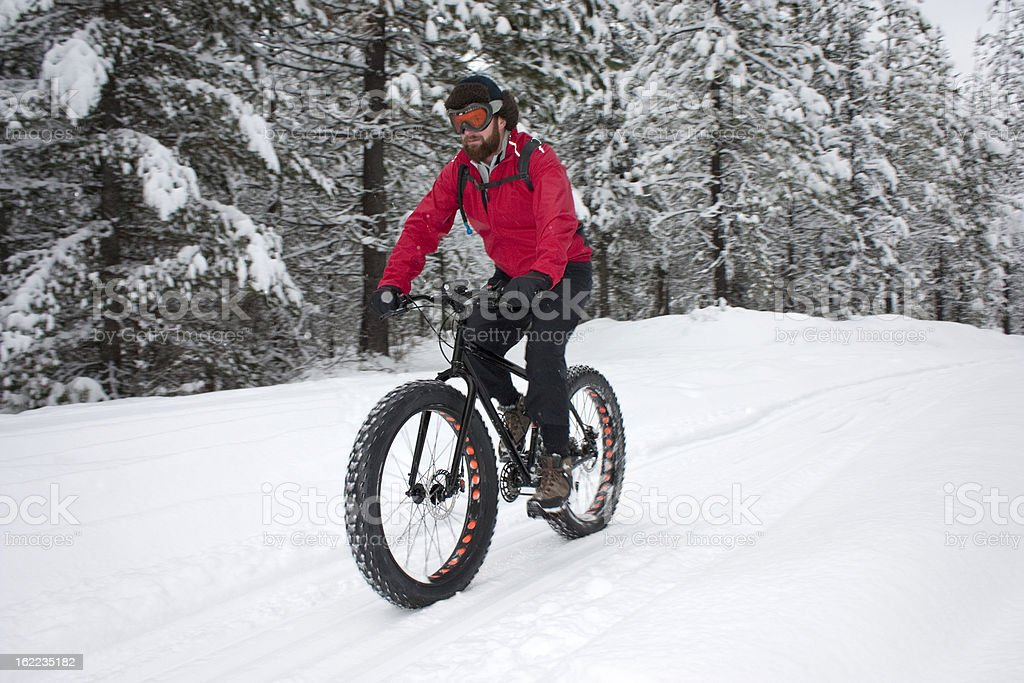 Cyclist riding snow covered trail on a snowbike. stock photo