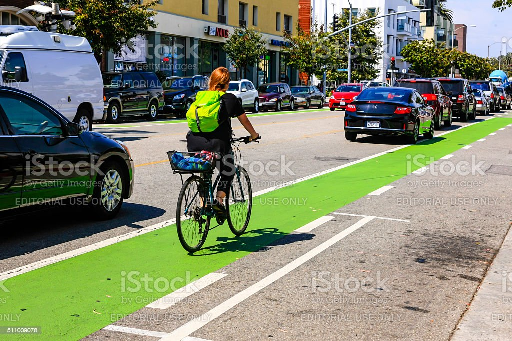 Cyclist riding the green bicycle lane in downtown Santa Monica stock photo
