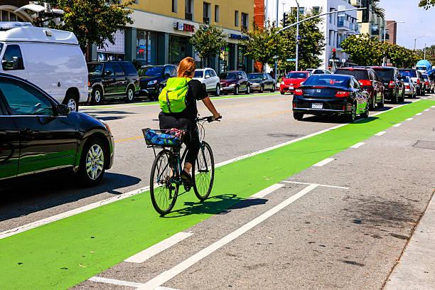 radfahrer reiten auf der grünen fahrradweg in der innenstadt von santa monica - fahrradwege stock-fotos und bilder