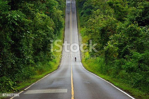 istock Cyclist riding the mountain road of Khao Yai National Park, Thailand. 674427154