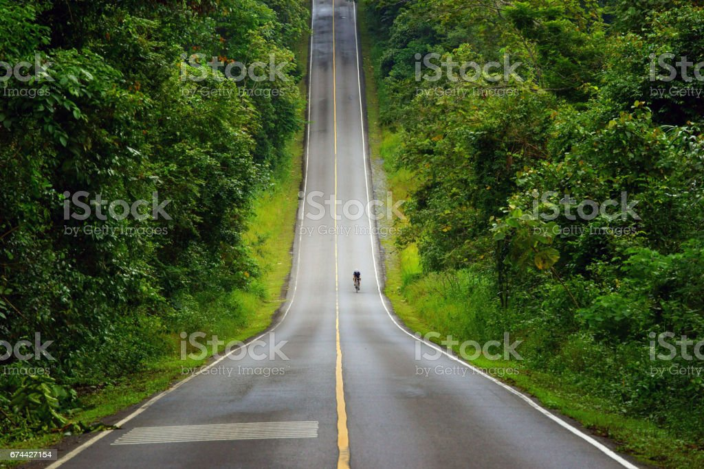 Cyclist riding the mountain road of Khao Yai National Park, Thailand. stock photo