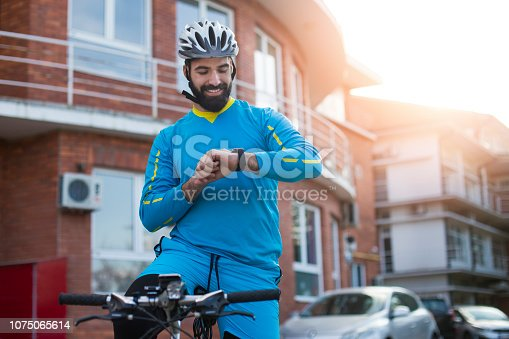 Young man riding a bicycle on a city street, setting up a smart watch. About 25 years old, Caucasian male.