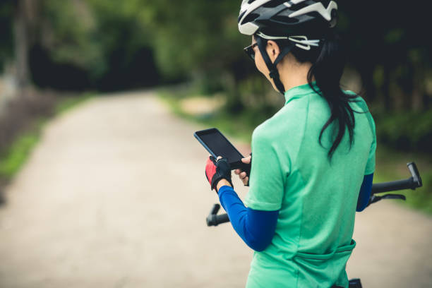Cyclist use smartphone for navigation when riding mountain bike on forest trail stock photo