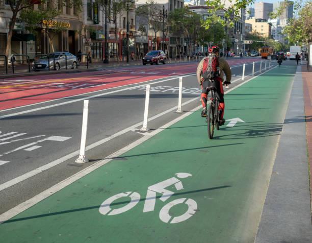 radfahrer nutzt einen ausgewiesenen radweg an der market street auf pendeln - fahrradwege stock-fotos und bilder