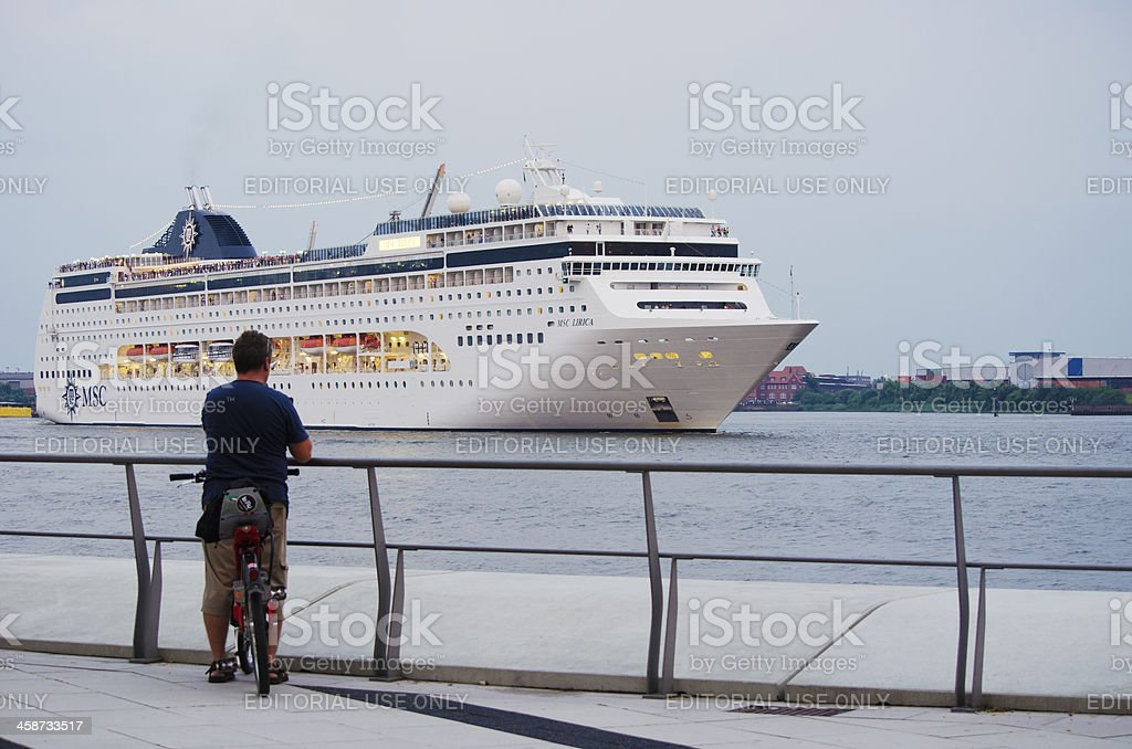 Cyclist watches cruise ship stock photo