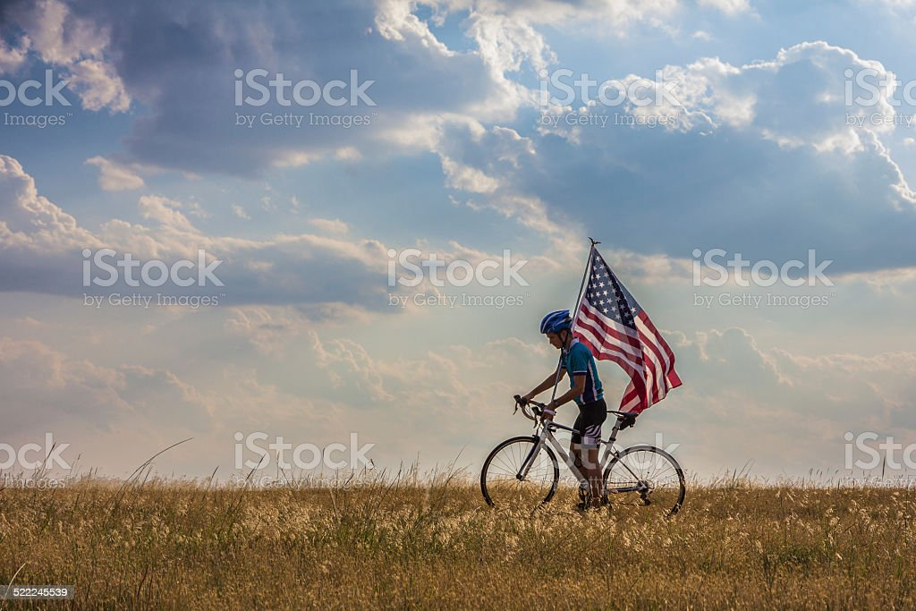 Cyclist Waving American Flag on Independance Day stock photo