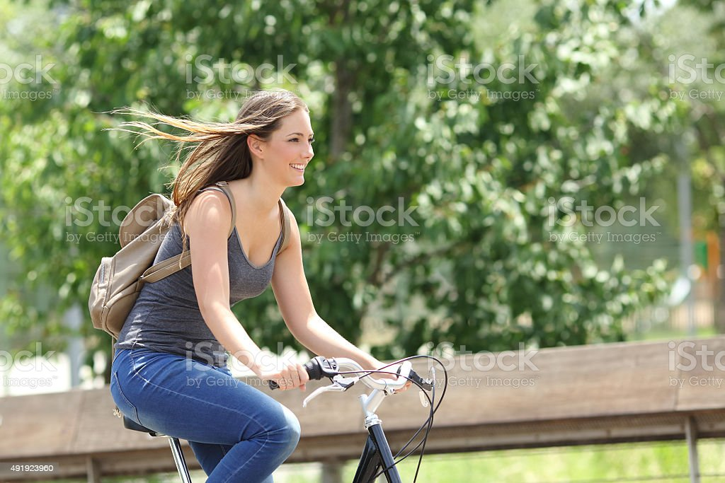 Cyclist woman riding bicycle in a park stock photo