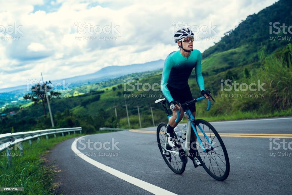 Cyclists are cycling, climbing up to the top. stock photo