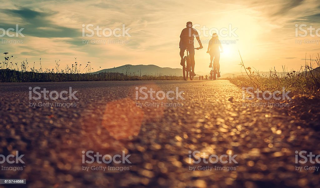 Cyclists are on the sunset road - foto de acervo