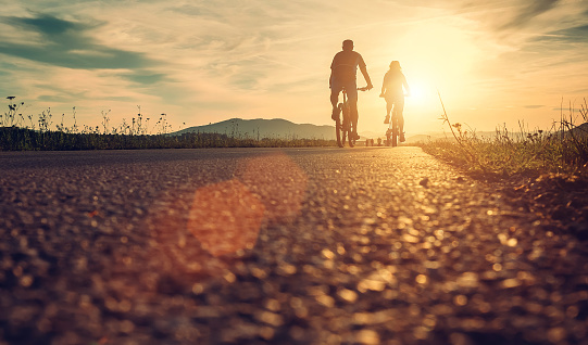 Cyclists Are On The Sunset Road Stock Photo - Download Image Now