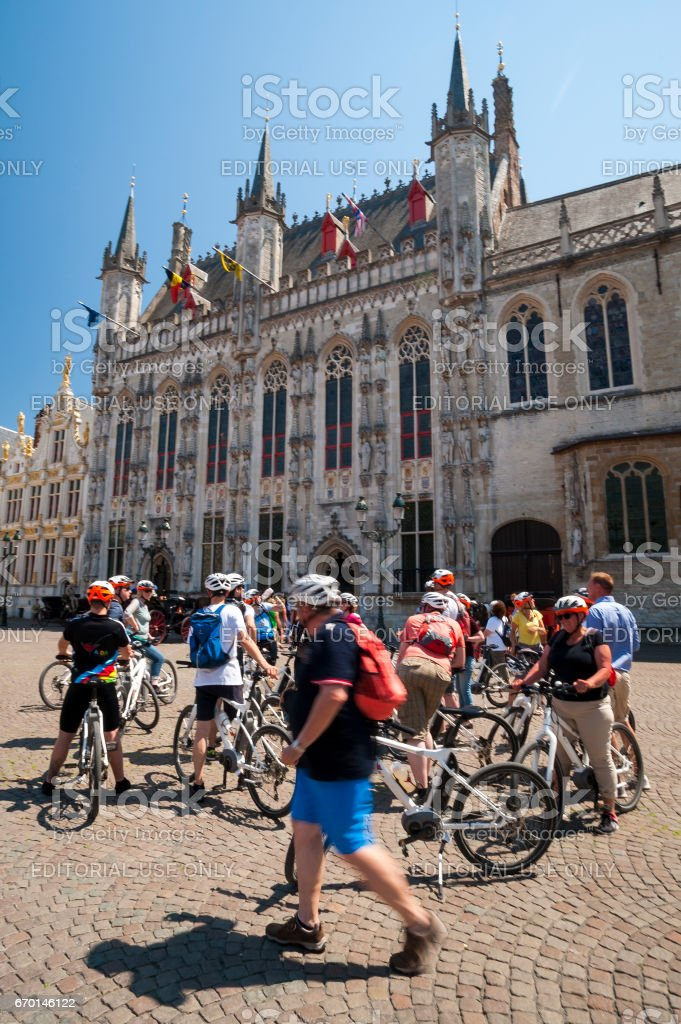 Cyclists at the City Hall in Bruges stock photo